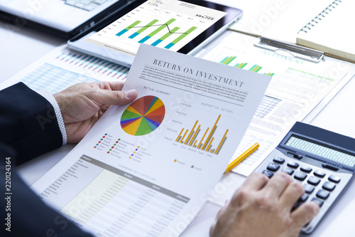 Fototapeta Businessman is deeply reviewing a financial report for a return on investment or investment risk analysis. obraz