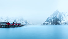 Blue Water Of Sea With Red Cabins On Shore