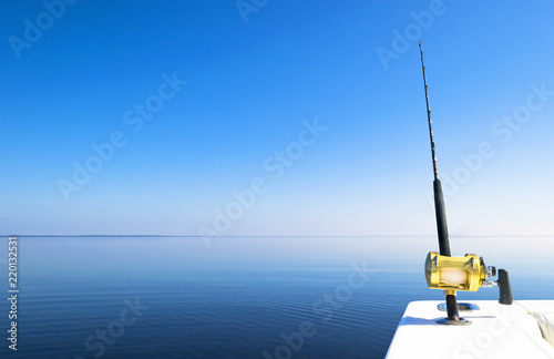 Poster Peche Fishing rod in a saltwater private motor boat during fishery day in blue ocean. Successful fishing concept