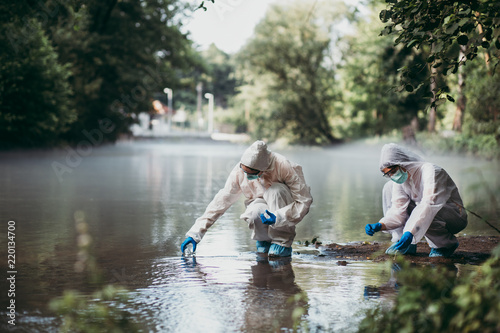 Two scientists in protective suits taking water samples from the river. - fototapety na wymiar