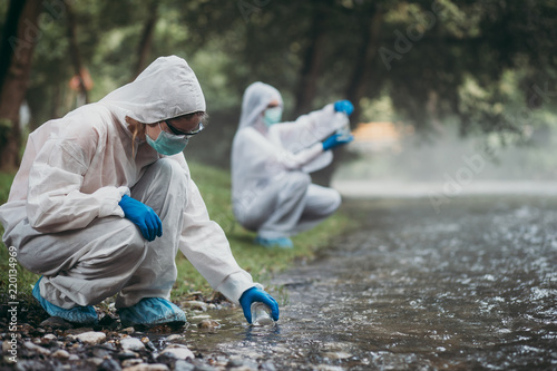 Photo  Two scientists in protective suits taking water samples from the river