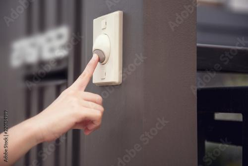 Obraz na plátne Closeup Finger of woman pressing doorbell home.