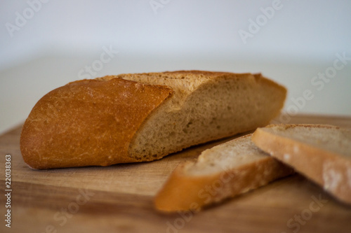 Poster Brood Fresh bread slice and cutting knife on rustic table