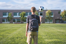 Teenager Tossing A Soccer Ball...
