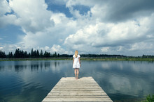 Back View Of A Blonde Woman Standing On Wooden Pier At The Lake. Color Tone Filter Effect Used.