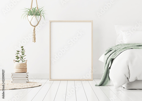Foto  Poster mockup with wooden vertical frame standing on floor in bedroom interior with bed, green plaid and plants on white wall