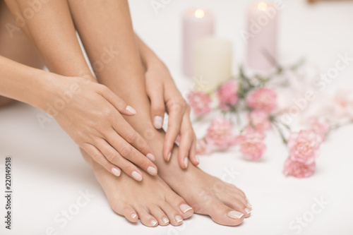 Montage in der Fensternische Pediküre The picture of ideal done manicure and pedicure. Female hands and legs in the spa spot.