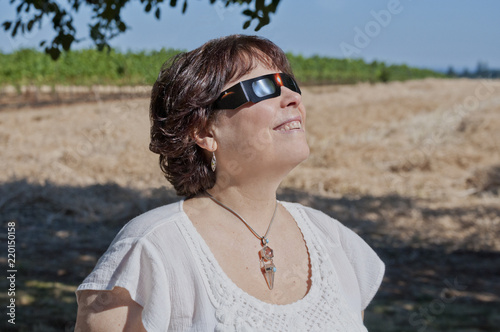 Woman viewing solar eclipse with solar glasses in country field/Woman looking at the solar eclipse with eclipse glasses