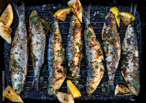 Grilled sardines in a herbal lemon marinade on a grill plate, top view. Grilled food, barbecue