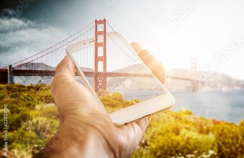 Optical illusion of bridge poking through phone