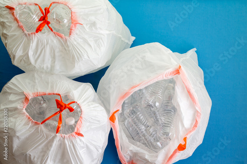 Fotografia, Obraz  Three white bags filled with plastic bottles