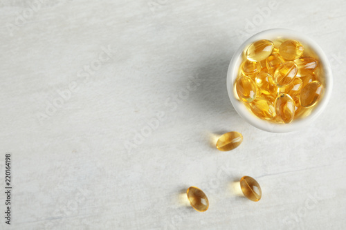 Bowl with cod liver oil pills and space for text on light background, flat lay