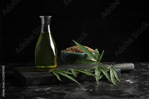 Bottle with hemp oil and fresh leaves on dark table. Space for text