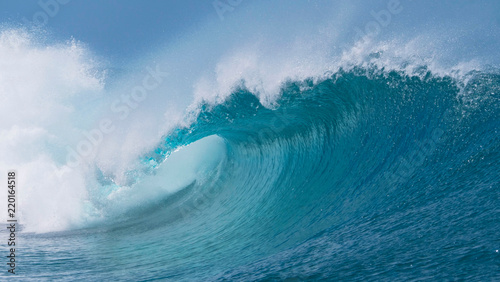 CLOSE UP: Beautiful deep blue tube wave in the Pacific curls on a sunny day.