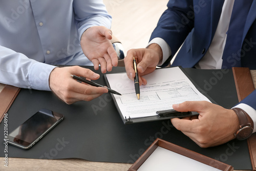 Lawyer working with client at table in office, focus on hands Wallpaper Mural
