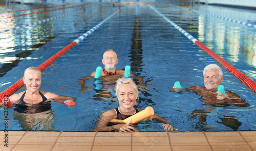 Fotografie, Obraz  Sportive senior people doing exercises in indoor swimming pool
