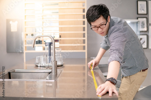 Young Asian Man Using Tape Measure For Measuring Granite Countertops On  Modern Kitchen Counter In Showroom