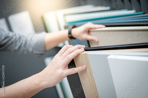 Fotografiet  Male hand choosing cabinet panel materials or countertops for built-in furniture design