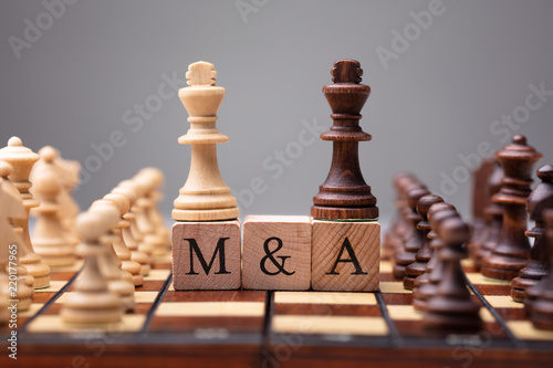 Foto King Chess Pieces With Mergers And Acquisitions Text