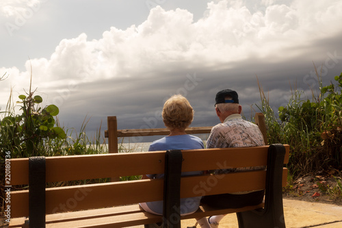 Fotografia, Obraz  An elderly couple enjoying a view of the ocean with a storm rolling in