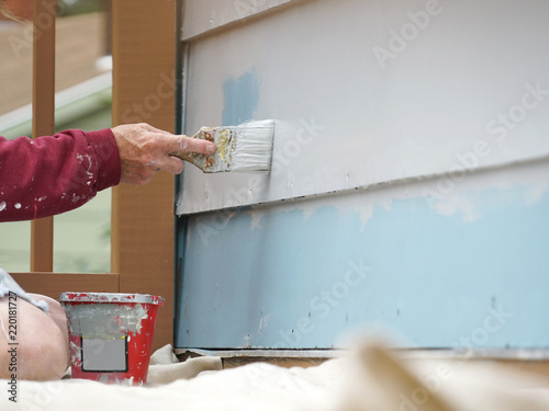 close up on handyman painting the exterior wall of the house