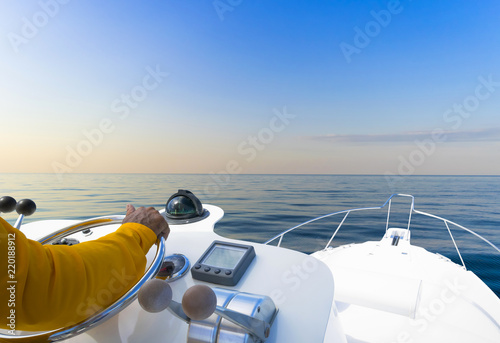 Photo Stands Ship Hand of captain on steering wheel of motor boat in the blue ocean during the fishery day. Success fishing concept. Ocean yacht