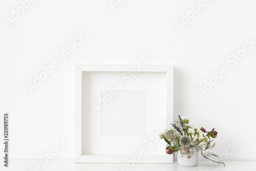Canvas Prints Textures White square portrait frame mockup with small bouquet of dried flowers in small white pot on white wall background. Empty frame, poster mock up for presentation design. Template frame for text