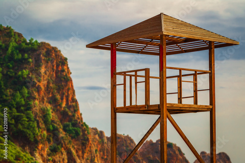 Poster Oceanië empty lifeguard station at a beach with a beautiful view oh the lawny mountain and sea