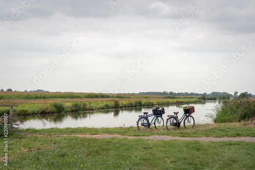 Fotografie, Tablou Dutch polder landscape with a stream and two bicycles