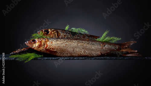 Smoked herring with dill on a black background.