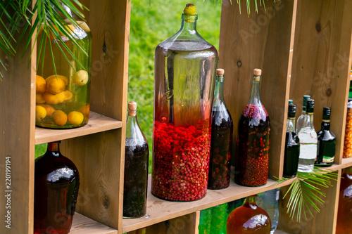 Fotografie, Obraz  Tincture bottles of lemon, currant, berries and rowanberries