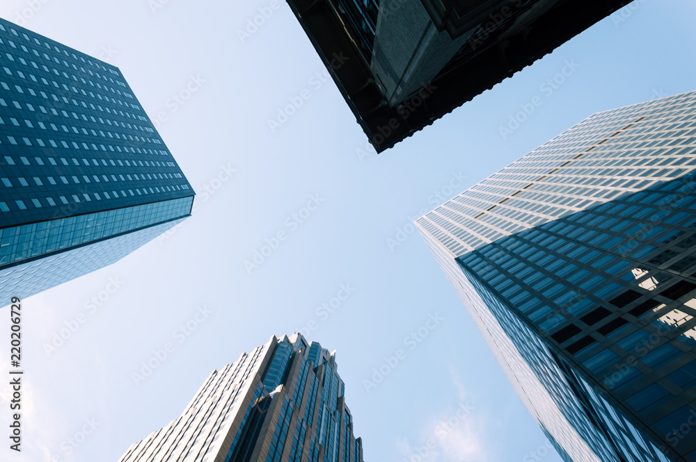 Fototapety, obrazy: Low angle view of skyscrapers against blue sky in New York