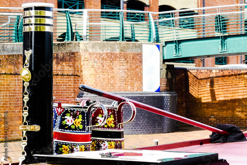 Fotografering  Top deck of canal boat, with colourful folk art bargeware metal jugs, polished brass mounted chimney stack and mop