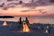 canvas print picture - Romantisches Paar sitzt bei einem privatem Abendessen am tropischen Strand und genießt den Sonnenuntergang
