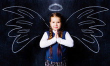 Schoolgirl Against Chalkboard, With Drawn Angel Wings