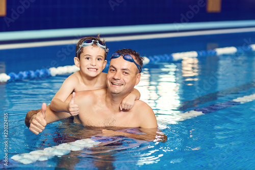 Fototapeta Young father and his little son having fun in an indoor swimming pool. obraz