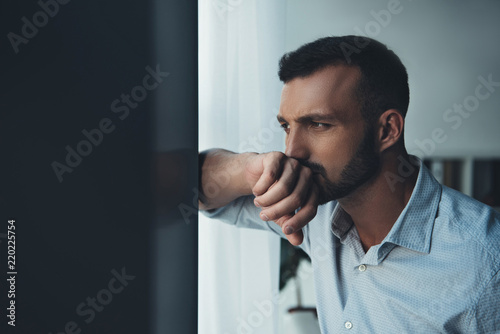 upset pensive man looking at window at home