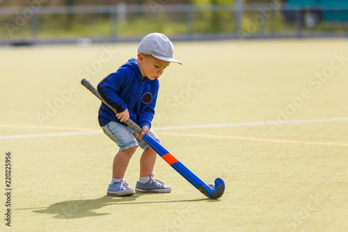 Small boy training playing field hockey with stick on the field