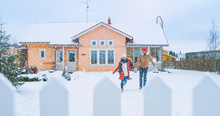 Young Beautiful Couple Running Out Of The House Into The Yard Covered With Fresh Snow, They Holing Hands. Happy Young People In Magical Winter Time.