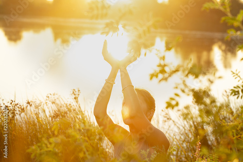 Papiers peints Fleur de lotus woman hands in mudra like in the palm of hands, at sunset on the lake in nature