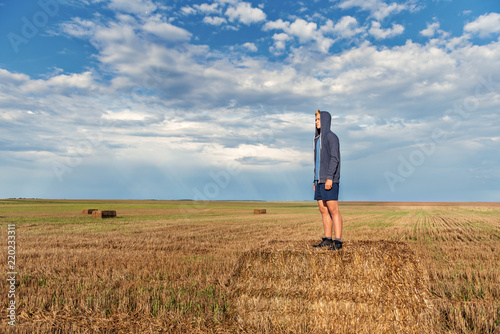 Valokuva  a young guy in a hood stands on a haystack in a wheat field after a rain with a