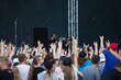 A crowd of people in front of the stage, hands in the air