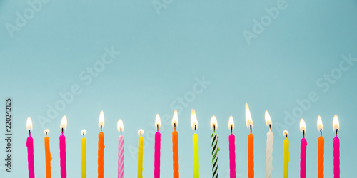 Fotografie, Obraz Set of many different color shape and pattern birthday candles burning in long row, isolated on blue