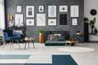 Leinwanddruck Bild - Carpet in grey spacious flat interior with blue armchair next to table near green futon. Real photo