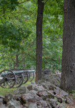Civil War Cannons Behind A Stone Wall In The Forest At Gettysburg PA