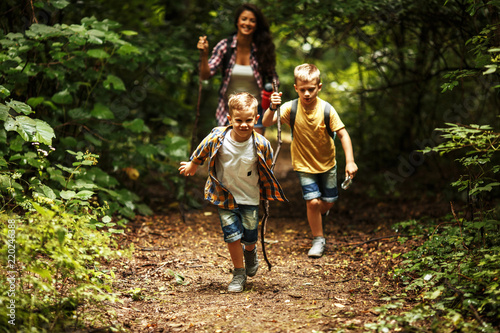Photographie Mother and her little sons hiking trough forest