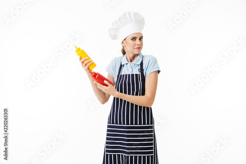 10de12edd7d Young astonished woman chef in striped apron and white hat thoughtfully  looking in camera with bottles