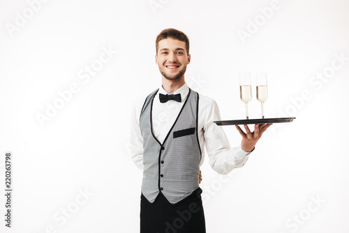 Joyful waiter in uniform happily looking in camera holding tray with glasses over white background isolated