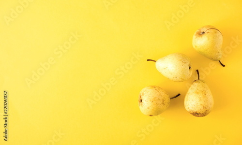 Yellow pear on a yellow background. Flat lay, top view, copy space