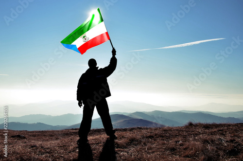 Fotografía  Successful silhouette man winner waving Equatorial Guinea flag on top of the mou